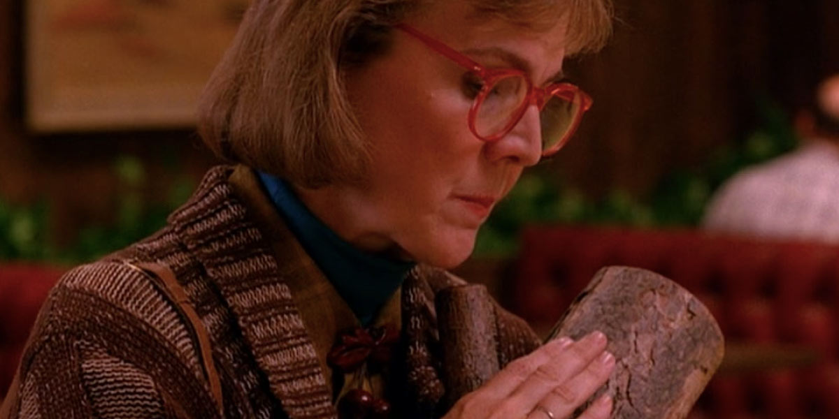 Still from the 1980s TV show Twin Peaks showing actress Catherine E. Coulson as the Log Lady stroking her pet log